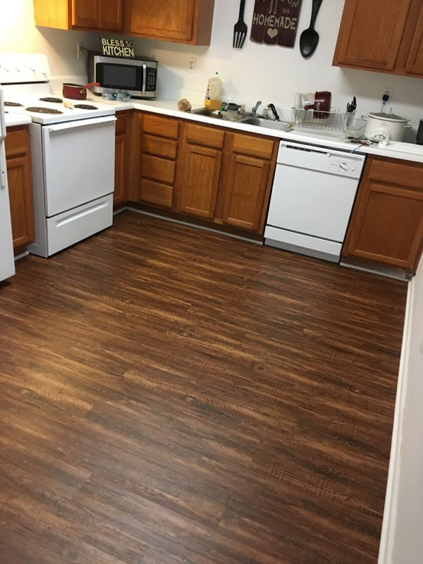 after new waterproof lvp in kitchen caramel pine